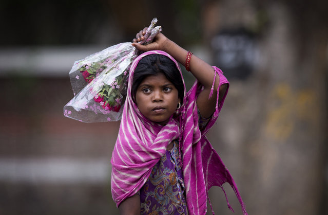 A young girl waits for cars to stop at the traffic light to sell flowers to commuters at a busy cross road in New Delhi, India, Wednesday, June 1, 2016. As they garner better sales due to sympathetic reasons, children are often forced by families to beg or sell small items for hours irrespective of weather conditions. (Photo by Saurabh Das/AP Photo)