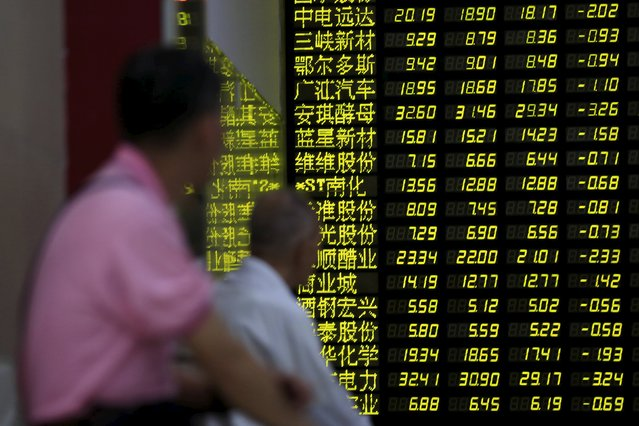 Investors look an electronic board showing stock information at a brokerage house in Shanghai, China, August 24, 2015. (Photo by Aly Song/Reuters)