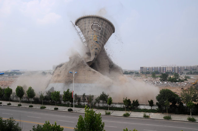 A cooling tower is seen under mechanical demolition in Binzhou, Shandong Province, China, July 13, 2016. (Photo by Reuters/China Daily)