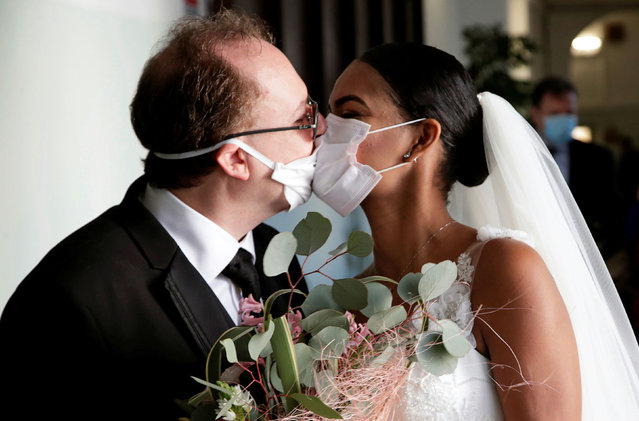 Newlyweds Diego Fernandes, 46 and Deni Salgado, 30, kiss through protective face masks at a wedding ceremony with only witnesses and no guests, as public gatherings are banned as part of Italy's lockdown measures to prevent the spread of coronavirus disease (COVID-19) in Naples, Italy, March 20, 2020. (Photo by Ciro De Luca/Reuters)