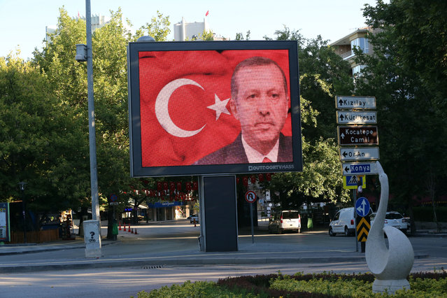 """A portrait of Turkey's President Recep Tayyip Erdogan appears on a billboard in Tunali Hilmi Street in Ankara, Turkey, Saturday, July 16, 2016. Forces loyal to Turkey's President Recep Tayyip Erdogan quashed a coup attempt in a night of explosions, air battles and gunfire that left dozens dead Saturday. Authorities arrested thousands of people as President Recep Tayyip Erdogan vowed those responsible """"will pay a heavy price for their treason"""". (Photo by Burhan Ozbilici/AP Photo)"""