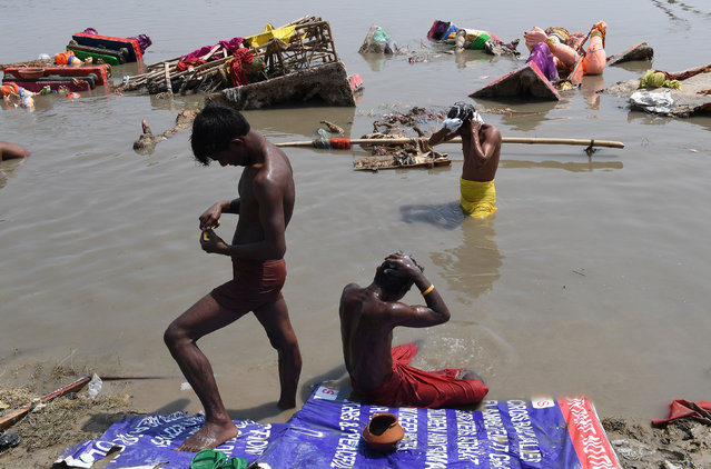 Indian men wash themselves amongst discarded religious offerings and frames for the idols of the elephant- headed Hindu deity Ganesha, immersed during the Ganesh Chaurthi festival, in the Yamuna river in New Delhi on September 6, 2017. (Photo by Prakash Singh/AFP Photo)