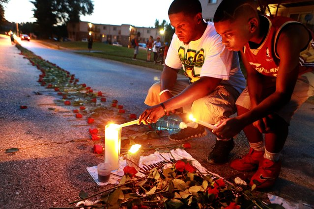 In this photo taken on Thursday, August 21, 2014, Theo Murphy, left, of Florissant, Mo., and his brother Jordan Marshall, 11, light candles at a memorial on Canfield Drive in Ferguson, Mo., where where unarmed Michael Brown was fatally shot by Ferguson Police Officer Darren Wilson. A small group of people, who preferred to remain anonymous,laid roses along the middle of the road that stretched about 60 yards. (Photo by Christian Gooden/AP Photo/St. Louis Post-Dispatch)