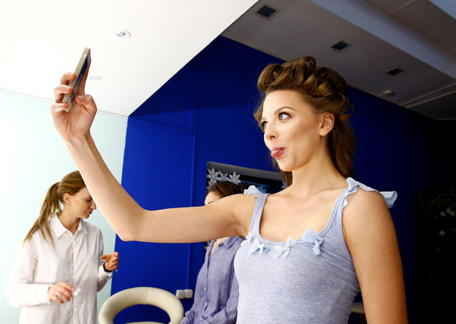 Belarussian rhythmic gymnast Melitina Staniouta takes a selfie as she has her make-up done in Minsk, May 29, 2016. (Photo by Vasily Fedosenko/Reuters)