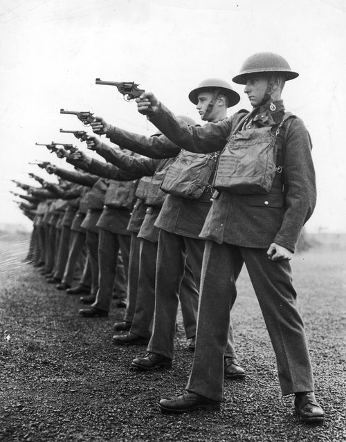 A line of soldiers firing handguns during a training session, circa 1920.  (Photo by Keystone)