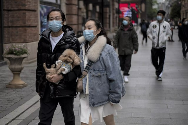 People wearing face masks walk along Hanjie shopping street in Wuhan, in China's central Hubei province on April 3, 2020. Wuhan, the central Chinese city where the coronavirus first emerged last year, partly reopened on March 28 after more than two months of near total isolation for its population of 11 million. (Photo by Noel Celis/AFP Photo)