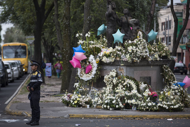 A police officer directs traffic near a memorial honoring 19 children and seven adults who died when a wing of a primary and secondary school collapsed in the recent earthquake, in Mexico City's southern Coapa district, Thursday, September 28, 2017. The memorial is located two blocks away from the Enrique Rebsamen School where according to the Mexican Navy, 11 children were rescued from the rubble. (Photo  by Moises Castillo/AP Photo)