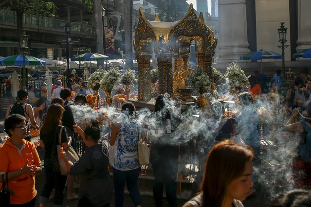 People pray after a religious ceremony at the Erawan shrine, the site of a recent deadly blast, after its was repaired, in central Bangkok, Thailand, September 4, 2015. (Photo by Athit Perawongmetha/Reuters)