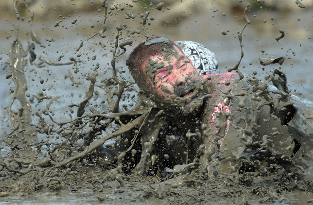 """A participant fights for the ball during a handball match at the so called """"Wattoluempiade"""" (Mud Olympics) in Brunsbuettel at the North Sea, Germany July 30, 2016. (Photo by Fabian Bimmer/Reuters)"""