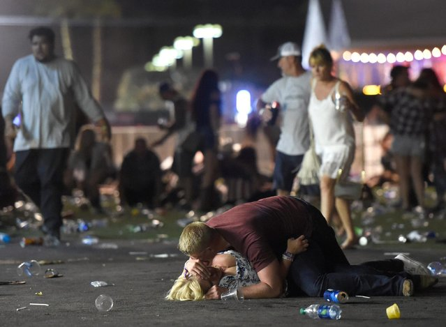 A man lays on top of a woman as others flee the Route 91 Harvest country music festival grounds after a active shooter was reported on October 1, 2017 in Las Vegas, Nevada. A gunman has opened fire on a music festival in Las Vegas, leaving at least 2 people dead. Police have confirmed that one suspect has been shot. The investigation is ongoing. The photographer witnessed the man help the woman up and they walked away. Injuries are unknown. (Photo by David Becker/Getty Images)
