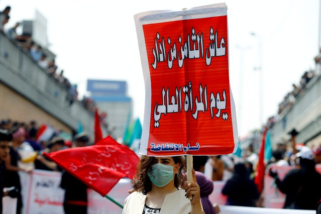 "A woman wearing a face mask, following an outbreak of coronavirus, holds a sign reading ""Long live the eighth of March the International Women's Day"" as she protests during the International Women's Day in Baghdad, Iraq, March 8, 2020. (Photo by Thaier Al-Sudani/Reuters)"