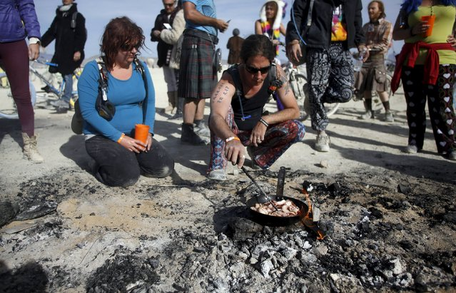 """Ashley (L) and Patience cook bacon for breakfast on the smoldering remains of the Man during the Burning Man 2015 """"Carnival of Mirrors"""" arts and music festival in the Black Rock Desert of Nevada September 5, 2015. (Photo by Jim Urquhart/Reuters)"""
