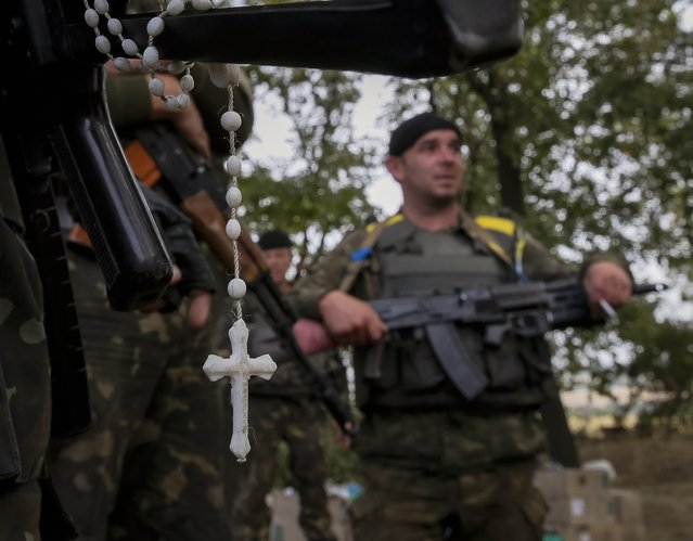 A rosary hangs from a machine gun as Ukrainian soldiers stand at their positions near the eastern Ukrainian town of Pervomaysk September 12, 2014. (Photo by Gleb Garanich/Reuters)