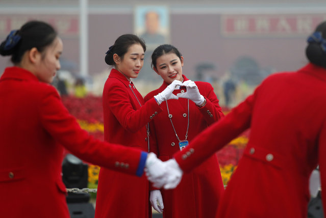 Ushers pose for photos at the Tiananmen Square during the opening of the 19th National Congress of the Communist Party of China at the Great Hall of the People in Beijing, China October 18, 2017. (Photo by Ahmad Masood/Reuters)