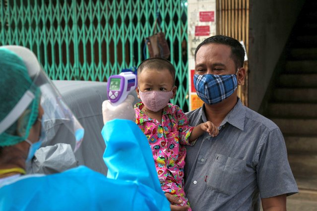 A medical staff member wearing protective gear amid concerns over the spread of the COVID-19 coronavirus takes the temperature of a young resident while going door-to-door for health check-ups in Yangon on May 17, 2020. (Photo by Sai Aung Main/AFP Photo)