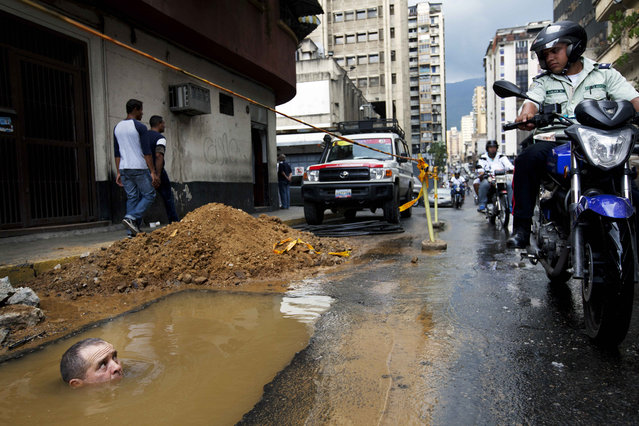 A worker is seen partially submerged under water as he tries to repair a broken pipe in Caracas, Venezuela, September 26, 2012. (Photo by Rodrigo Abd/AP Photo)