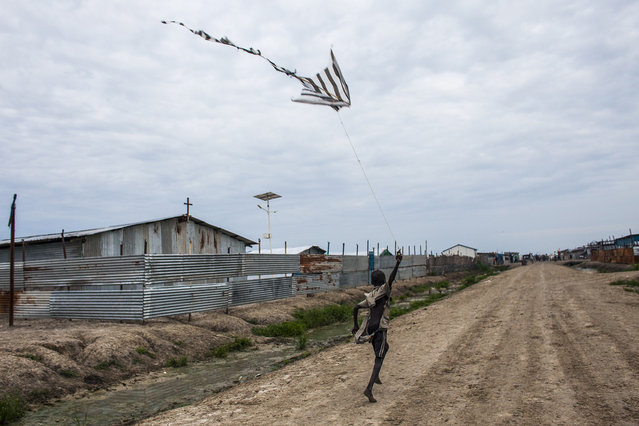 A boy flies a kite made from plastic bags in the Protection of Civilians (POC) site at the United Nations Mission in South Sudan (UNMISS) base in Malakal, South Sudan on Thursday, July 7, 2016. The POC site houses close to 32,000 displaced people mainly from the Shilluk and Nuer tribes in the Upper Nile State. In February of this year, violence broke out inside the camp as many armed members of the Dinka tribe, who resided in the camp at the time, along with members of the SPLA who infiltrated the camp, attacked the Shilluk and Nuer in the camp destroying large sections of the site resulting in many wounded and dead. (Photo by Jane Hahn/The Washington Post)