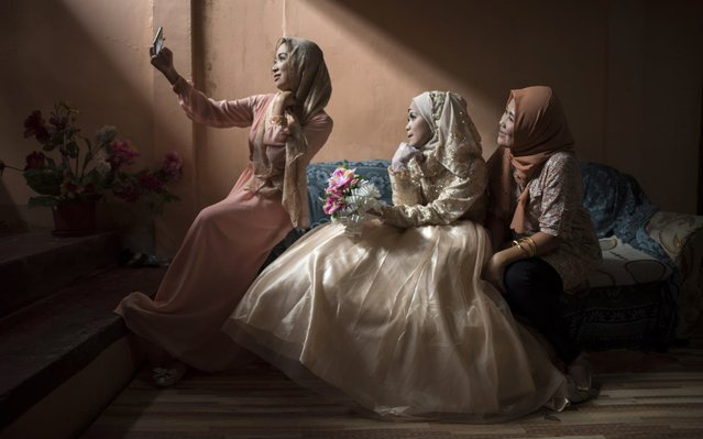 Bride Katty Malang Mikunug with friends, takes a photo before the wedding on October 21, 2017 in Saguiaran in Lanao del Sur, southern Philippines. Paulo Mamayo Ambor, 22, a resident of Marawi who got displaced by the fighting between government troops and IS-inspired militants, weds Katty Malang Mikunug, 22, a resident of an adjacent town in Saguiaran. Philippines President Rodrigo Duterte declared Marawi liberated, following the death of Abu Sayyaf leader Isnilon Hapilon and one of the Maute brothers, Omar Maute, after nearly five months of fierce urban battle inside the besieged city. The fighting started May 23, and left more than 1,000 people dead, whilst displacing at least 400,000 people. (Photo by Jes Aznar/Getty Images)