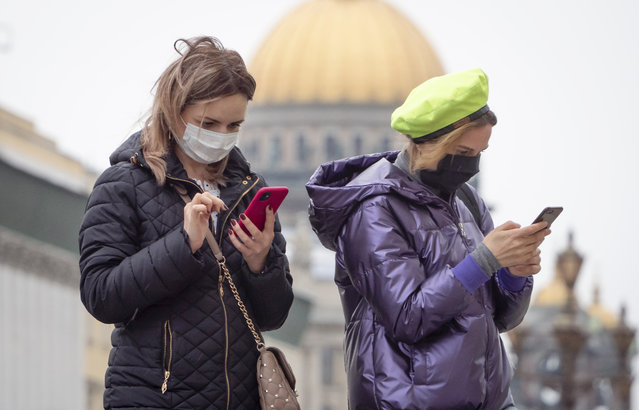 Women wearing face masks to protect against coronavirus look at their smartphones in downtown St.Petersburg, Russia, Monday, May 11, 2020. Russian President Vladimir Putin has declared an end to a nationwide partial economic shutdown but noted that some restrictions will remain. (Photo by Dmitri Lovetsky/AP Photo)