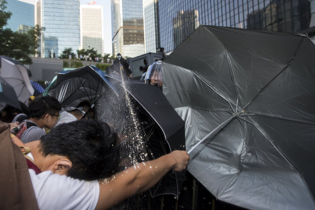 Riot police target pro-democracy students with pepper spray after hundreds of protesters stormed into a restricted area in Hong Kong September 27, 2014. (Photo by Tyrone Siu/Reuters)