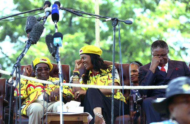 Zimbabwe's President Robert Mugabe, left, speaks with his wife Grace while his Vice President Phelekezela Mpoko, right, looks on during a solidarity rally in Harare, Wednesday, November 8, 2017. Zimbabwe's president said Wednesday he fired his deputy and longtime ally for scheming to take power, including by consulting witch doctors. Now Mugabe's wife appears poised for the role. (Photo by AP Photo/Stringer)