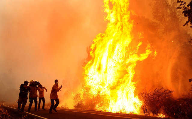 A news crew runs from flames southeast of Middletown, Calif., on Tuesday, September 15, 2015, as winds kick up the Valley fire. (Photo by Wally Skalij/Los Angeles Times/TNS)