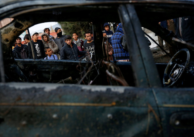 People look at a destroyed vehicle after a suicide bomb attack in Kabul, Afghanistan November 16, 2017. (Photo by Mohammad Ismail/Reuters)