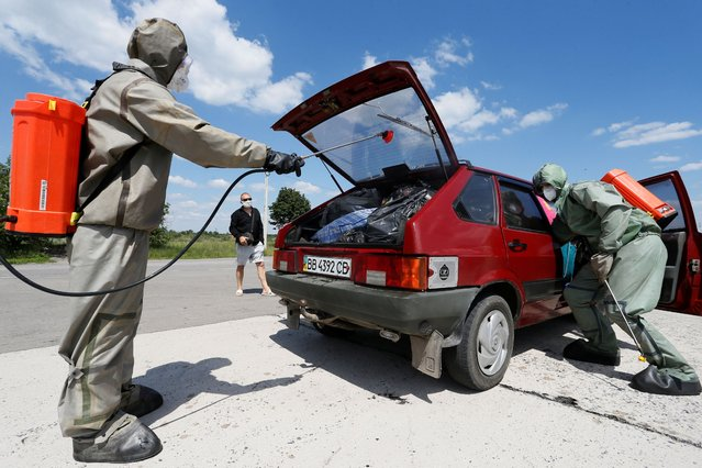 Specialists wearing protective gear carry out the disinfection of a car at a checkpoint on a way linking Ukrainian government-controlled territory and the self-proclaimed Donetsk People's Republic, near the settlement of Olenivka in Donetsk Region, Ukraine June 25, 2020. The checkpoint was temporarily closed due to the coronavirus disease (COVID-19) outbreak and then reopened. (Photo by Alexander Ermochenko/Reuters)