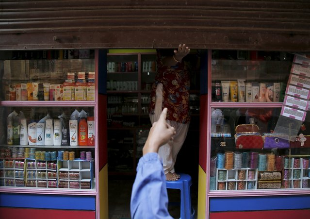 An opposition supporter protesting against the proposed constitution forces a shopkeeper to close a shop during a nationwide strike, called by the opposition parties in Kathmandu, Nepal September 20, 2015. (Photo by Navesh Chitrakar/Reuters)