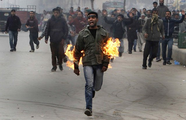 A Kashmiri Shiite mourner runs after he set himself on fire during a Muharram procession in Srinagar, India, November 23, 2012. The Kashmiri man was protesting a police ban on religious processions marking the Muslim month of Muharram in Indian-controlled Kashmir's main city. Police said that clashes erupted when troops tried to stop groups of Shiite Muslims from gathering. (Photo by Associated Press)