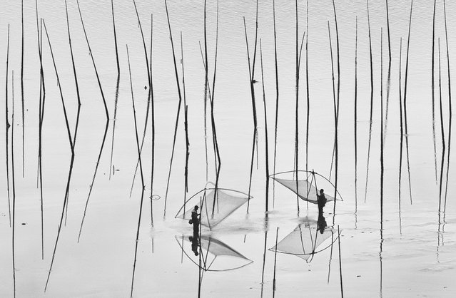 """Two Fishermen: The shoal is one of the most fascinating places in Xiapu, China. Fishermen farm fish, shrimp, and oysters and plant seaweed along this coast area"". (Photo and comment by Peng Jiang/National Geographic Photo Contest via The Atlantic)"