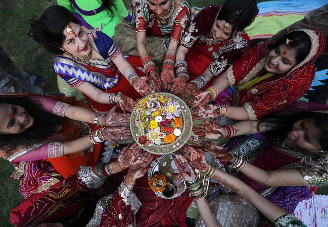 Women with their hands decorated with henna paste pose for pictures as they pray during the Hindu festival of Karva Chauth in the western Indian city of Ahmedabad October 11, 2014. Married Hindu women observe a one-day fast and offer prayers for the well-being of their husbands during the festival. The fast begins before sunrise and ends after they worship the moon in the evening. (Photo by Amit Dave/Reuters)
