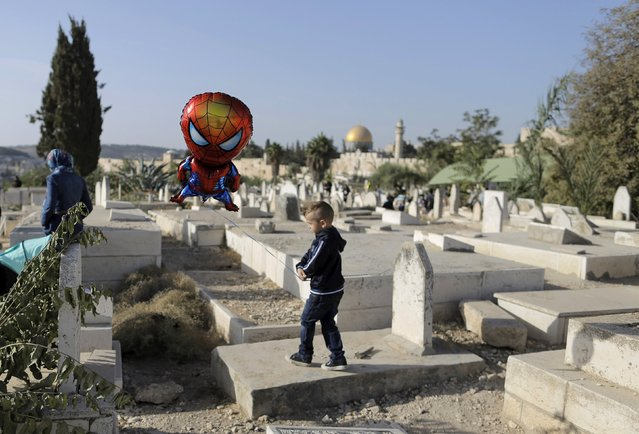 The Dome of the Rock is seen in the background as a Palestinian boy holds a balloon in a Muslim cemetery just outside Jerusalem's Old City during Eid al-Adha September 24, 2015. (Photo by Ammar Awad/Reuters)