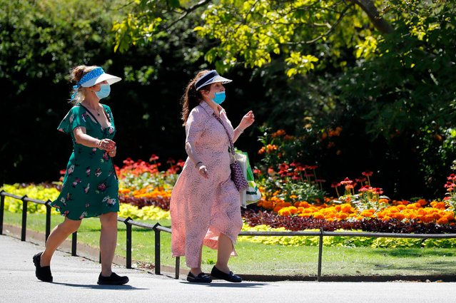 Women wearing facemasks walk through Regents park in central London on July 30, 2020. (Photo by Tolga Akmen/AFP Photo)