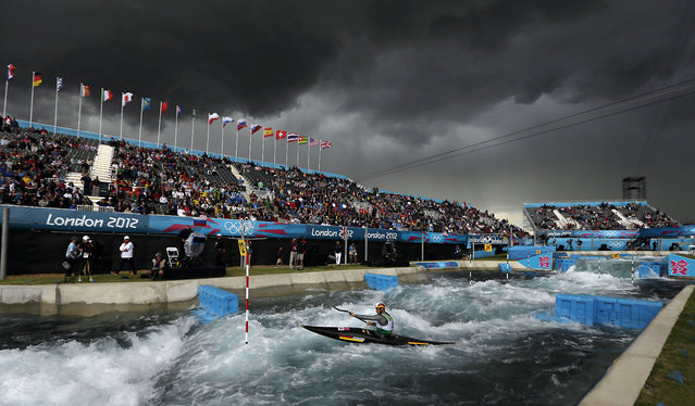 The sky turns black before a heavy rain shower as Germany's Hannes Aigner competes in the heats of the K-1 men's canoe slalom at Lee Valley Whitewater Center, at the 2012 Summer Olympics, July 29, 2012, in London. (Photo by Kirsty Wigglesworth/AP Photo)