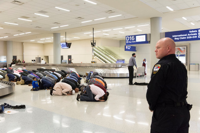 People gather to pray in baggage claim during a protest against the travel ban imposed by U.S. President Donald Trump's executive order, at Dallas/Fort Worth International Airport in Dallas, Texas, January 29, 2017. (Photo by Laura Buckman/Reuters)