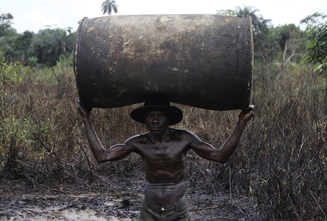 Ebiowei, 48, carries an empty oil container on his head to a place where it would be filled with refined fuel at an illegal refinery site near river Nun in Nigeria's oil state of Bayelsa November 27, 2012. (Photo by Akintunde Akinleye/Reuters)
