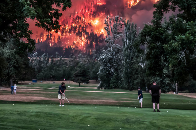 The Eagle Creek wildfire burns as golfers play at the Beacon Rock Golf Course in North Bonneville, Washington, September 4, 2017. (Photo by Kristi McCluer/Reuters)