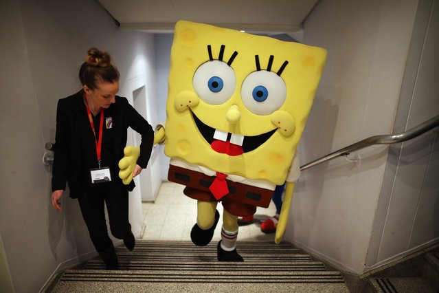 A Sponge Bob Square Pants character is helped up a flight of stairs  during the 2013 London Toy Fair at Olympia Exhibition Centre on January 22, 2013 in London, England. The annual fair which is organised by the British Toy and Hobby Association, brings together toy manufacturers and retailers from around the world.  (Photo by Dan Kitwood)