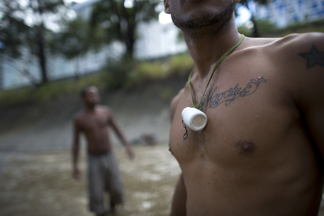 In this December 5, 2017 photo, a medicine bottle hangs from a river scavenger's neck, where he keeps the small pieces of gold and other precious metals he finds on the bottom of the polluted Guaire River, in Caracas, Venezuela. A surge of young men and boys turn each day to the Guaire for survival in Venezuela's deepening crisis, scavenging from the river that runs the distance of Caracas. (Photo by Ariana Cubillos/AP Photo)