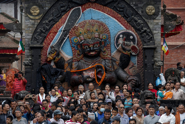 Nepalese devotees attend the flag-pole hoisting ceremony on the first day of the Indra Jatra festival, as a symbol of unity, victory and power in Hanuman Dhoka, Kathmandu, Nepal, 13 September 2016. The eight-day-long Indra Jatra festival celebrates Indra, the king of gods and god of rains. The festival also marks the end of the monsoon. Kumari, the living goddess, is also taken around parts of the capital city in a religious procession during the festival, The Indra Jatra is very important festival for the Kathmandu based ethnic Newari community. (Photo by Narendra Shrestha/EPA)