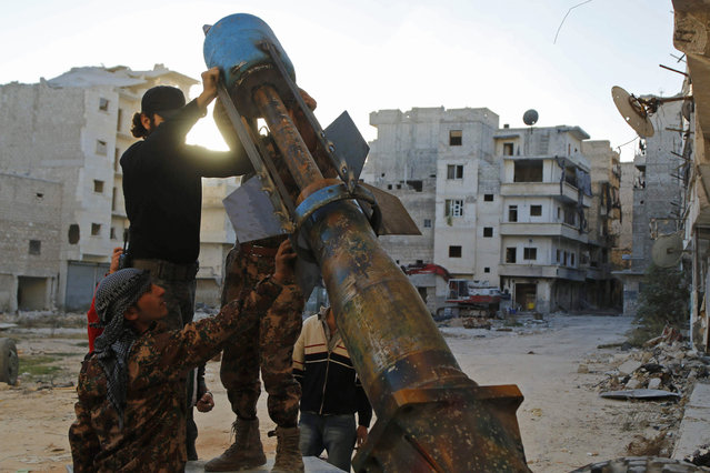 """""""Free Syrian Army"""" fighters prepare a locally-made weapon launcher during clashes with forces loyal to Syria's President Bashar al-Assad on the Amerya front in Aleppo November 5, 2014. (Photo by Hosam Katan/Reuters)"""