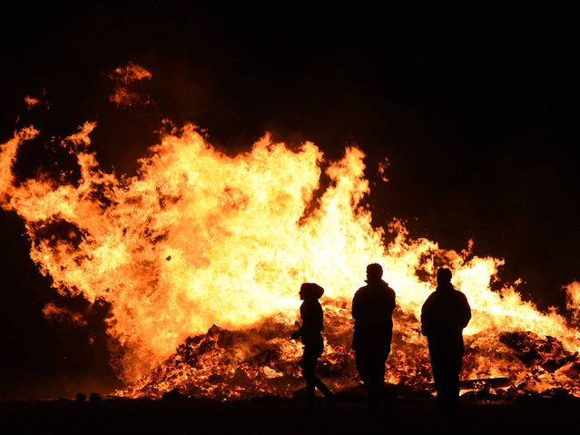 Fireworks technicians stand in front of a large bonfire after a public fireworks display in Driffield, Northern England, on November 1, 2014, held prior to the Bonfire Night on November 5. (Photo by Oli Scarff/AFP Photo)