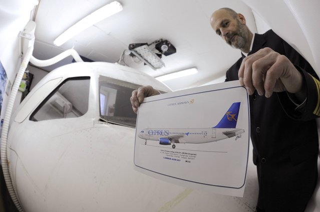 Igor Perne, 53, an electronic engineer and a member of the International Virtual Aviation Organisation (IVAO), shows a picture of the Cyprus Airways Airbus 320 which he used to make his flight simulator (back) in Nova Vas November 13, 2014. (Photo by Srdjan Zivulovic/Reuters)