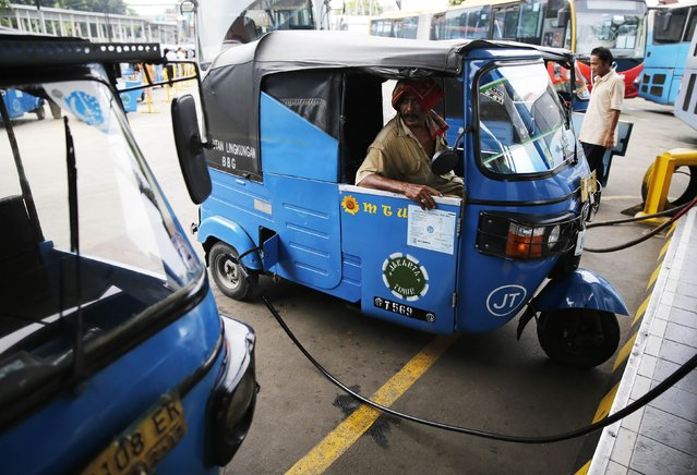 A driver sits inside his Bajaj auto rickshaw as he fills gas at a state-owned Pertamina gas station in Jakarta November 28, 2014. Indonesia's president picked the president director of cement firm PT Semen Indonesia, Dwi Soetjipto, as the new head of state energy firm Pertamina, a cabinet minister said on Friday. (Photo by Reuters/Beawiharta)