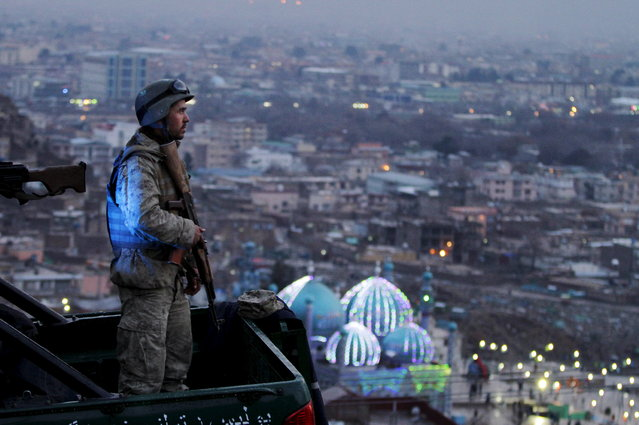 An Afghan Army soldier secures the hill overlooking the Kart-e Sakhi mosque in Kabul, Afghanistan, Wednesday, March 20, 2013. Thousands of Afghans will celebrate Nowruz on Thursday, March 21, 2013 to mark the first day of spring and the beginning of the year on the Iranian calendar. (Photo by Ahmad Jamshid/AP Photo)
