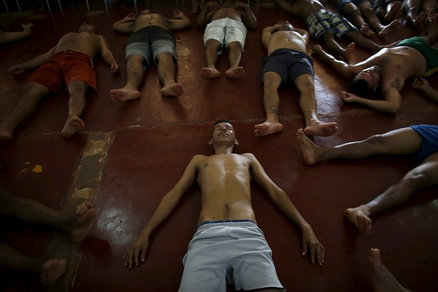 Prisoners do yoga stretches and breathing exercises after a half-day visit by their families as part of the ACUDA programme, at a complex of ten prisons in Porto Velho, Rondonia State, Brazil August 28, 2015. (Photo by Nacho Doce/Reuters)