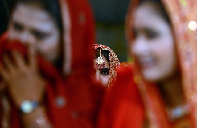 Pakistani brides attend a mass marriage ceremony in Karachi late March 26, 2013.  Some 110 couples participated in the mass wedding ceremony organised by a local charity welfare trust Al Ghousia. (Photo by Asif Hassan/AFP Photo)