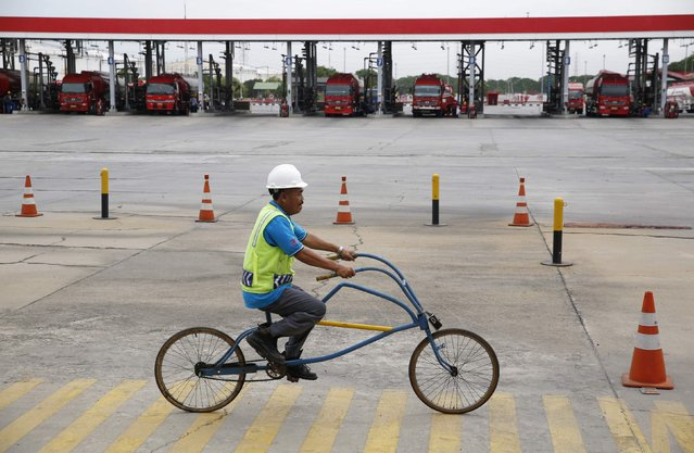 A worker rides his bicycle past fuel trucks loading their cargo at a state-owned Pertamina fuel depot in Jakarta December 3, 2014. (Photo by Darren Whiteside/Reuters)