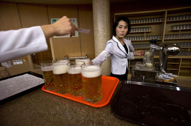North Korean waitresses prepare to serve beer at the Mansugyo Soft Drink restaurant in Pyongyang, on December 20, 2012. North Korean leader Kim Jong Un ordered the reconstruction of the restaurant that stood for decades along the Taedong river. The restaurant specializes in seven flavors of beer, cocktails, coffee and snack food. (Photo by Ng Han Guan/AP Photo)